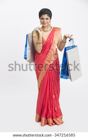 Happy smiling young traditional woman with shopping bags on white background. - stock photo
