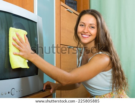 Happy smiling young woman cleaning TV with rag at home