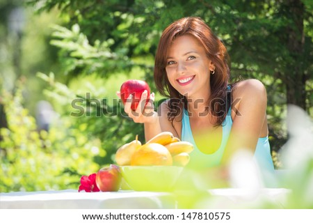 Happy Smiling Young Woman Eating Organic Apple at her Garden - stock photo