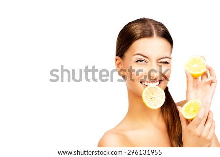 Happy smiling young woman holding fresh juicy lemons. Healthy lifestyle. Healthy eating. Fruits and vegetables. Isolated over white.  - stock photo
