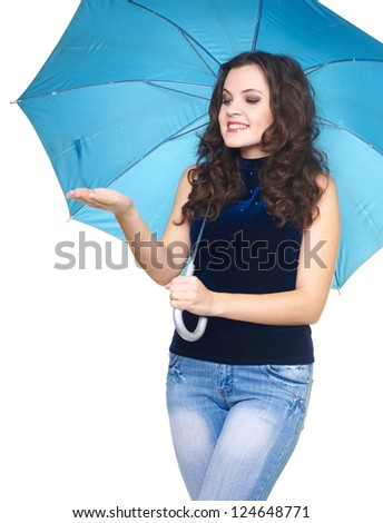 Happy smiling young woman in a blue shirt standing under a blue umbrella. Woman looks at a drop of rain in her hand. Isolated on white background