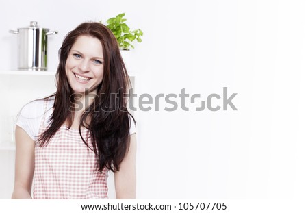 happy smiling young woman in a kitchen - stock photo