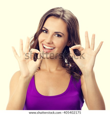 Happy smiling young woman in casual smart lilac clothing, showing okay gesture - stock photo