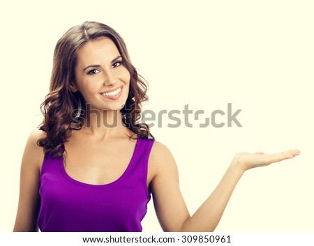 Happy smiling young woman in casual smart lilac clothing, showing something or copyspace for text or slogan - stock photo
