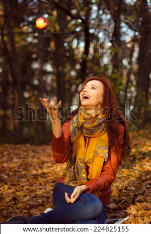 Happy Smiling Young Woman Juggling Apple in the park - stock photo