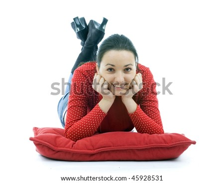 happy, smiling  young woman lying on the red pillow - stock photo