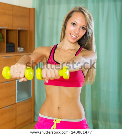 Happy smiling young woman training with dumbbells at home  - stock photo