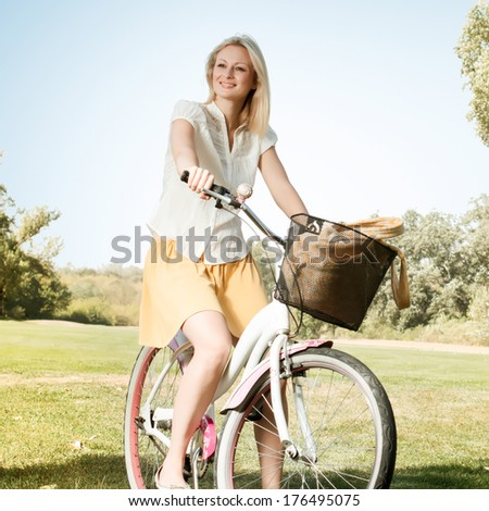 Happy smiling young woman with a bicycle in the park. - stock photo