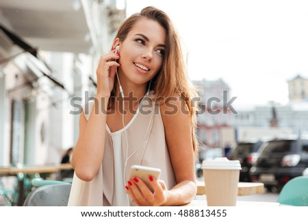 Happy smiling young woman with earphones listen music and holding smartphone while sitting at cafe outdoors