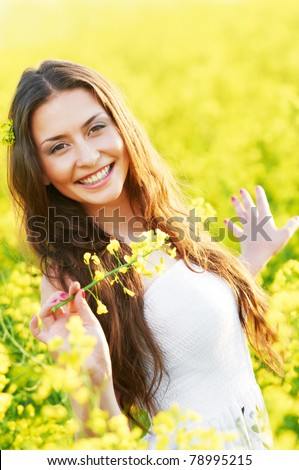 Happy smiling young woman with flower bouquet over yellow green rapeseed meadow - stock photo