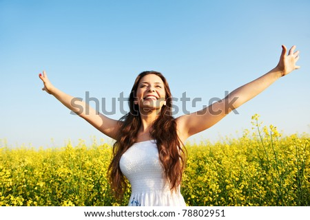 Happy smiling young woman with hands up over yellow green rapeseed meadow