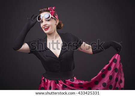 Happy smiling young woman with pin-up make-up and hairstyle posing on black background - stock photo