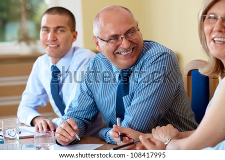 Happy smilling senior businessman during meeting with other co-workers