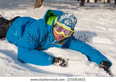 Happy snowboarder resting on the snow - stock photo
