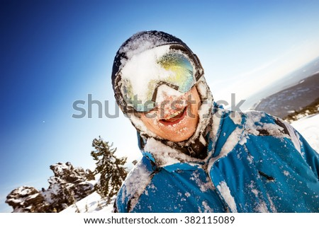 Happy snowboarder smiling after falling to snowdrift. Sheregesh resort, Siberia, Russia - stock photo