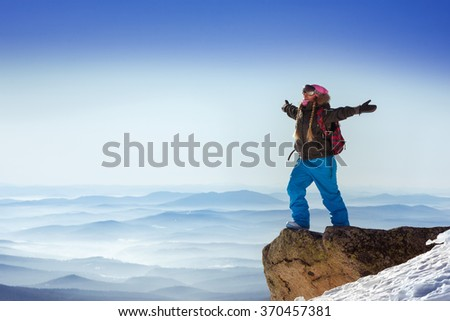 Happy snowboarder stands on big rock on mountains backdrop. Sheregesh resort, Siberia, Russia - stock photo
