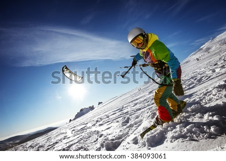 Happy snowboarder with kite lies in snowdrift. Sheregesh resort, Siberia, Russia - stock photo