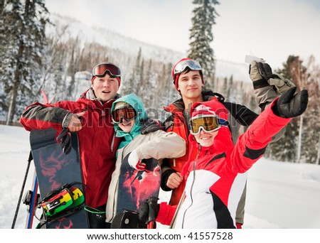 Happy snowboarding team in winter mountains - stock photo