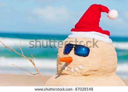 Happy snowman at the beach with sun glasses. His right arm is visible as well - stock photo