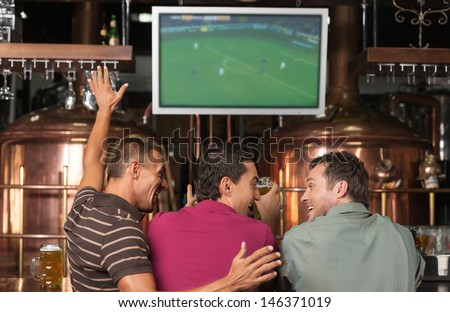 Happy soccer fans. Three happy soccer fans watching a game at the pub - stock photo