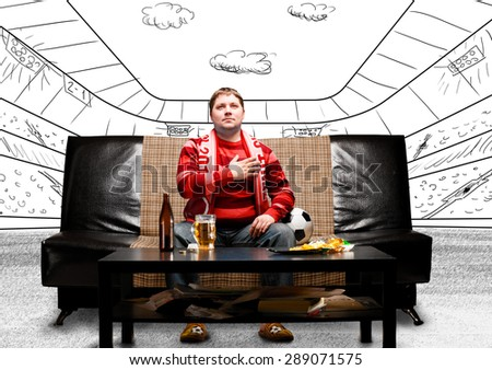 happy soccer or football fan with hand on heart on sofa at sketch stadium - stock photo