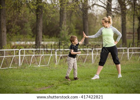 Happy son and mother are doing exercises in the summer park. on the stadium, outdoor. Sport activities with children. Healthy lifestyle. Fitness exercises. Young mother and son together - stock photo