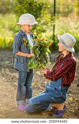 Happy son and mother gardening together and taking care of nature. focus on boy - stock photo