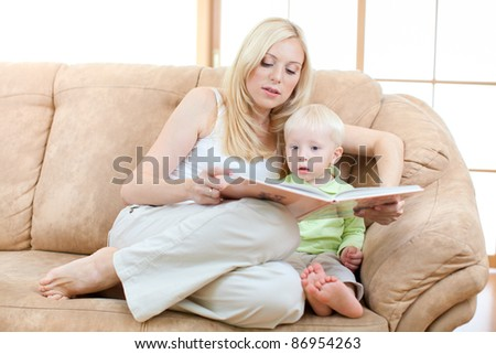 Happy son and mother lying on sofa looking directly to camera. - stock photo