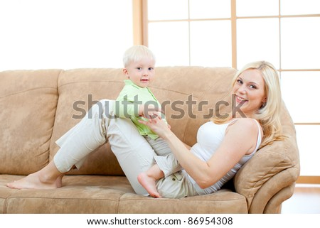 Happy son and mother lying on sofa looking directly to camera.