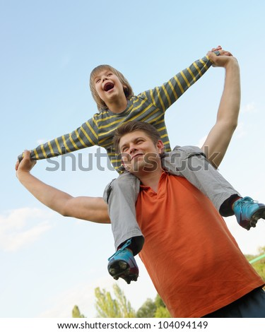 Happy son on the shoulders of the father. On the background of blue sky - stock photo