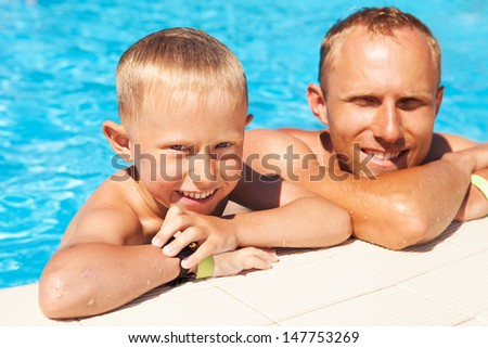 Happy son swims with his father into the pool - stock photo