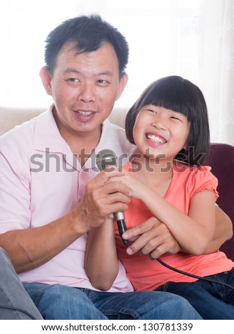 Happy Southeast Asian family living lifestyle. Portrait of a Asian father and daughter singing karaoke through microphone in the living room - stock photo