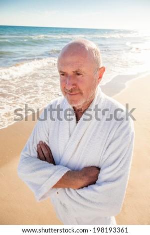 happy spa senior walking down the beach - stock photo