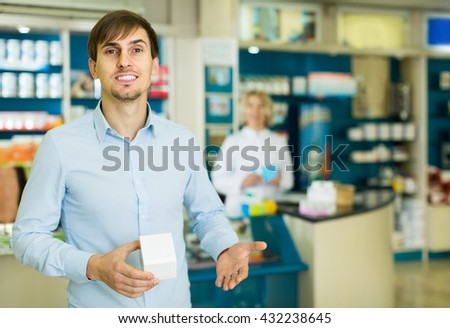 happy spanish handsome man   in pharmacy drugstore   - stock photo