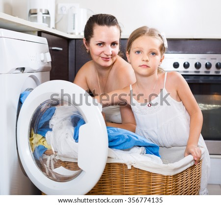 Happy spanish  housewife and her daughter with linen near washing machine  - stock photo