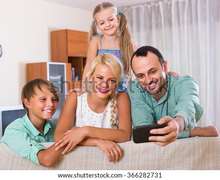 happy spanish parents with two children posing in home interior