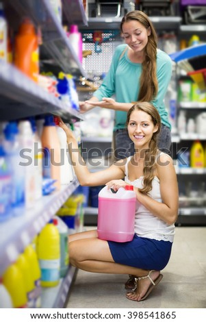 happy spanish  people choose some detergents in the shop - stock photo