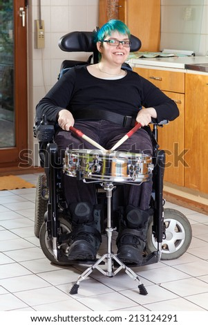 Happy spastic young woman with infantile cerebral palsy due to birth complications confined to a multifunctional wheelchair beating on a drum as part of her therapy smiling at the camera - stock photo