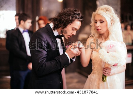 Happy spiritual bride & groom exchanging wedding rings in church - stock photo