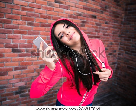 Happy sportive cute woman listening music on smartphone over brick wall
