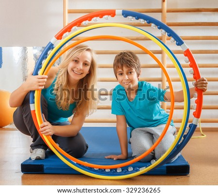 Happy, sports family, mother and son looking through hula hoops - stock photo