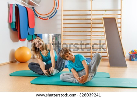 Happy, sports family, mother and son perform gymnastic exercises. - stock photo