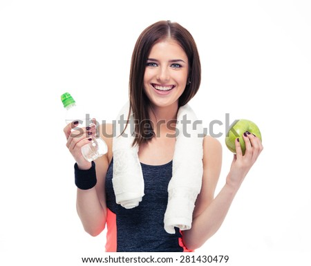 Happy sports woman holding apple and bottle with water isolated on a white background. Looking at camera - stock photo