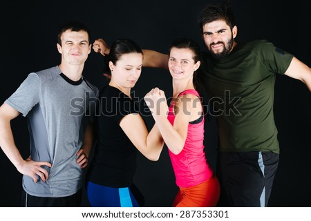 Happy sporty couples showing their biceps and smiling while standing close to each - stock photo