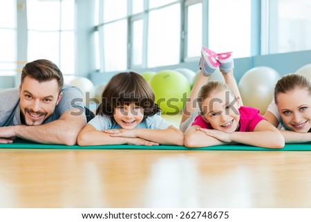 Happy sporty family. Happy family bonding to each other while lying on exercise mat in sports club - stock photo