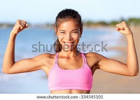 Happy sporty fitness woman flexing muscles on beach. Smiling young is wearing pink sports bra. Female is showing her strength and healthy lifestyle on sunny day. - stock photo