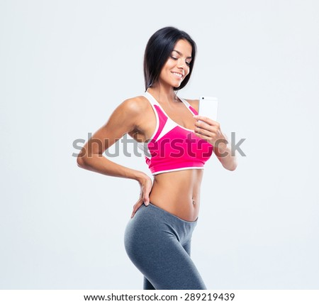 Happy sporty woman making photo on smartphone over gray background - stock photo
