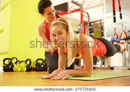 Happy sporty woman training in gym with coach. - stock photo