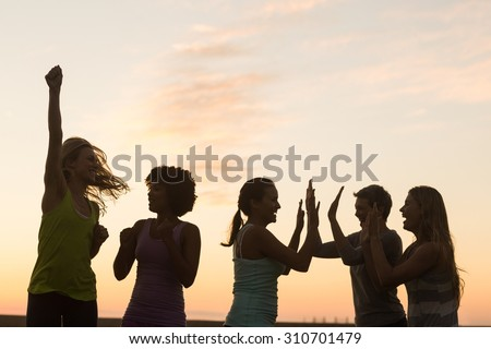 Happy sporty women cheering against sunset in parkland - stock photo