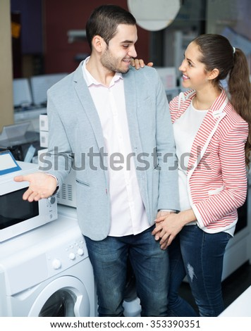 Happy spouses choosing new clothes washing machine in marketplace